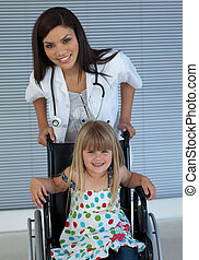 Portrait of a little girl on a wheelchair and a young doctor