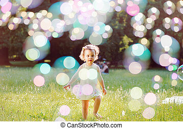 Portrait of a little girl playing the soap bubbles