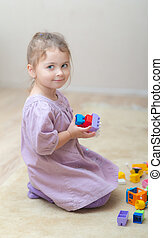 girl playing with plastic toys