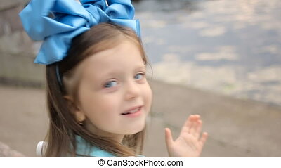 portrait of a little girl three years with the blue bow on her head, which is smiling
