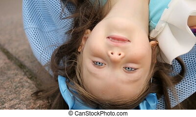 portrait of a little girl three years with the blue bow on her head which is lying sideways