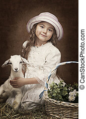Portrait of a little girl with a baby goat