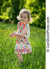 Portrait of a little girl with a lollipop