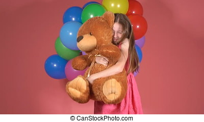 Portrait of a little girl with a toy bear. slow motion. The child holding soft toy in hands, laughing and smiling