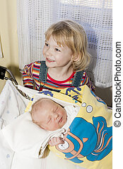 portrait of a little girl with her newborn baby sister in maternal hospital