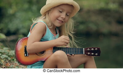Portrait of a little girl with long blond hair playing guitar in the forest near the river