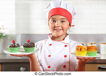 Portrait of a little girl with plates of muffins