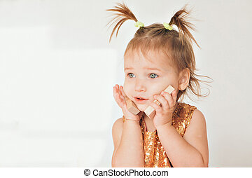portrait of a little girl with tails on white background. Baby plays with toys