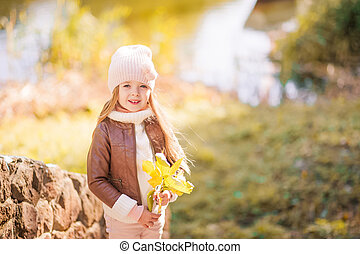 Portrait of a little girl with yellow leaves in her hands. Baby girl in pink hat and leather jacket