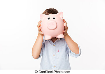 Portrait of a little kid covering his face with a piggy bank...
