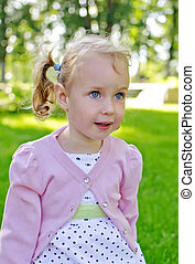 Portrait of a little lovely girl sitting in park