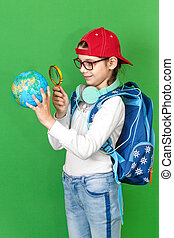 Portrait of a little schoolgirl with a backpack holding a globe in her hands
