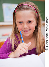 Portrait of a little schoolgirl writing on a book