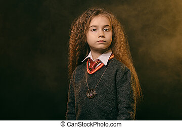 Portrait of a little witch girl with long brown hair, dressed in dark clothes, posing against a black smoky studio background. Close-up.