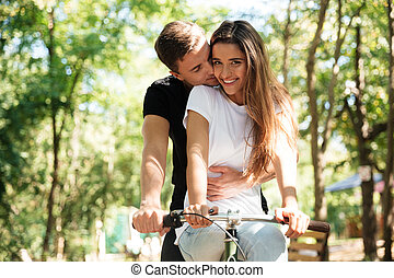 Portrait of a lovely couple riding on a bicycle together