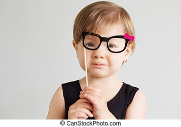 Portrait of a lovely little girl with funny paper glasses against a white background
