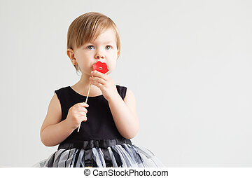 Portrait of a lovely little girl with funny paper lips against a white background