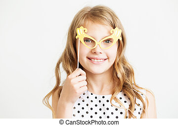 Portrait of a lovely little girl with funny party paper glasses