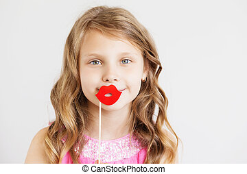 lovely little girl with funny red paper lips against a white background