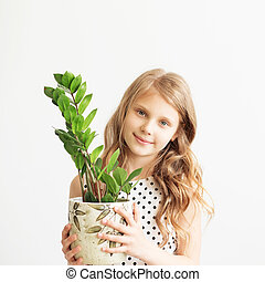Portrait of a lovely little girl with green houseplant...