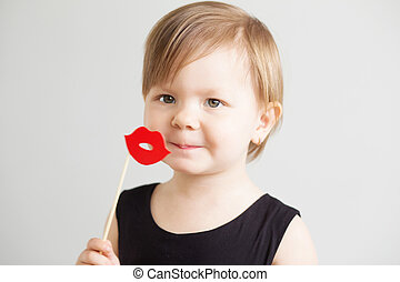 Portrait of a lovely little girl with funny red paper lips