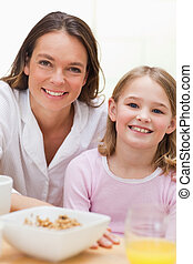 Portrait of a lovely mother and her daughter having breakfast