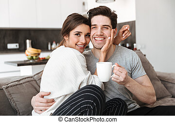 Portrait of a lovely young couple drinking coffee