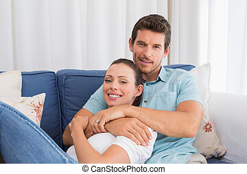 Portrait of a loving couple sitting on couch