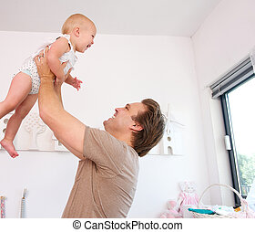 Portrait of a loving father lifting and playing with cute...