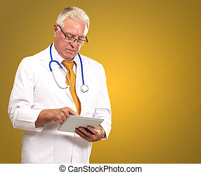 Portrait Of A Male Doctor Holding A Tab On A Yellow Background