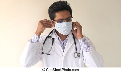 portrait of a male doctor in face mask looking at camera
