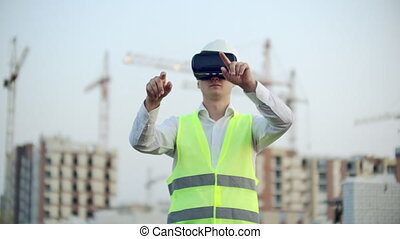 Portrait of a male inspector analyzing the work of builders using virtual reality glasses. A man in a helmet and a protective vest stands in VR glasses and moves his hands.