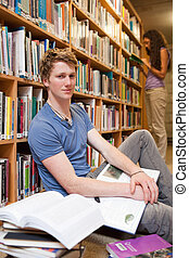 Portrait of a male student with books while his classmate is reading in a library