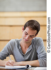 Portrait of a male student writing on a notepad