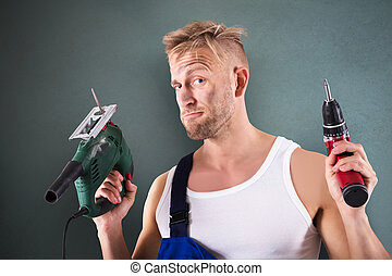 Technician Holding Electric Drill And Screwdriver