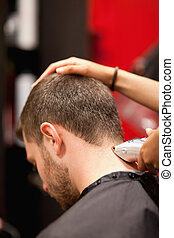 Portrait of a male young student having a haircut with a ...