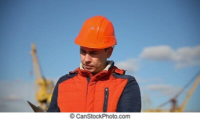 Portrait of a man builder in orange helmet looks instruments against the blue sky and building