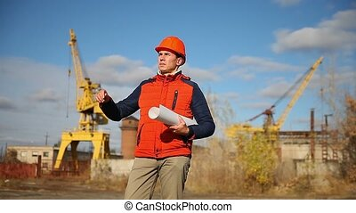 Portrait of a man builder in orange helmet looks instruments project against the blue sky and building