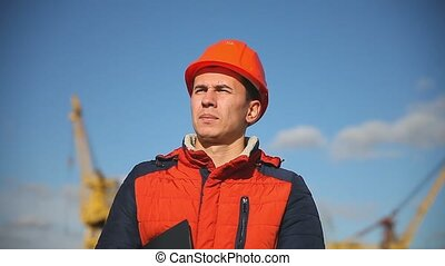 Portrait of a man construction worker in an orange helmet on a background of blue sky and construction