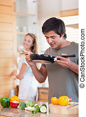Portrait of a man cooking while his fiance is washing the dishes in their kitchen