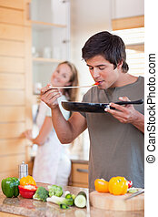 Portrait of a man cooking while his girlfriend is washing the dishes in their kitchen