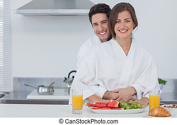 Portrait of a man embracing his wife in the kitchen
