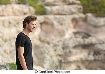 Portrait of a man exploring and looking away in the mountain