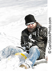 Portrait of a man full of snow sitting on a slegde in deep snow