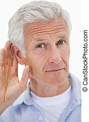Portrait of a man giving his ear against a white background
