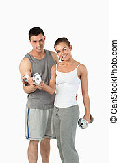 Portrait of a man helping a gorgeous woman to work out