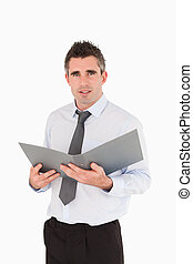 Portrait of a man holding a binder against a white...