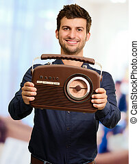 Portrait Of A Man Holding Vintage Radio