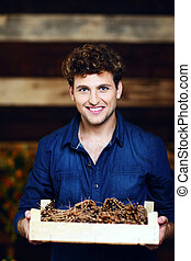 Portrait of a man holding wooden box with pine cones