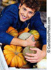 Portrait of a man hugging pumpkins